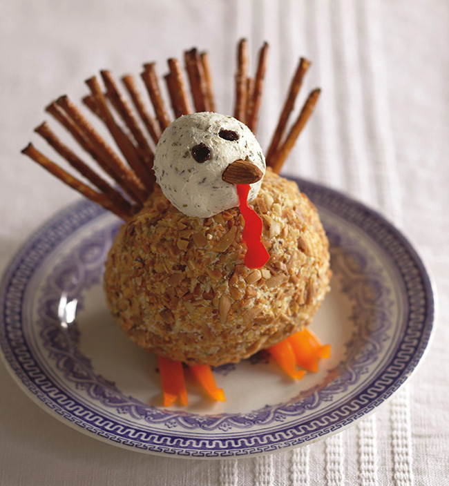 While they wait, treat them to a deliciously festive appetizer that looks just like a turkey. Inspired by Michelle Buffardi's Great Balls of Cheese, this turkey cheese ball appetizer is adorable.