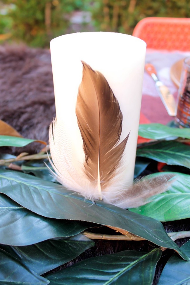 Lovely Feather Decorated Candles on this fabulous outdoors tablescape- See More Woodsy Tablescape Details On B. Lovely Events